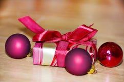 有红色的小礼物盒在木背景鞠躬 免版税库存照片
