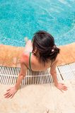有红色的少妇晒伤了在她的坐在游泳池附近的肩膀的皮肤 库存照片