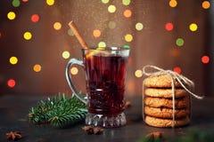 有红色的杯为圣诞节假日仔细考虑了酒或桑格里酒和姜饼曲奇饼 在光圣诞节背景的不可思议的饮料 库存图片