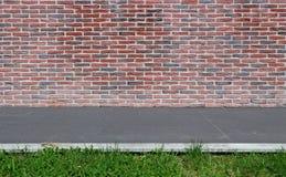 有红色的砖墙和黑色、一条灰色石瓦片边路和草小条  E 免版税库存照片