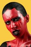 有红色皮肤的意想不到的女孩在一片黄色背景和白色牙和黑嘴唇 库存照片