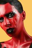有红色皮肤的意想不到的女孩在一片黄色背景和白色牙和黑嘴唇 图库摄影