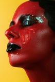有红色皮肤的意想不到的女孩在一片黄色背景和白色牙和黑嘴唇 免版税库存照片