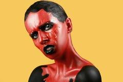 有红色皮肤的意想不到的女孩在一片黄色背景和白色牙和黑嘴唇 库存图片