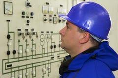 有红色盔甲控制仪表的工程师在能源厂 免版税库存照片