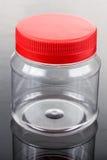 有红色盖子的透亮塑料PVC瓶子 库存图片