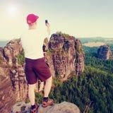 有红色盖帽的游人在两只手做与手指的框架 有大背包立场的远足者在森林上的岩石观点 库存照片