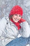 有红色盖帽的美丽的妇女在雪天。 库存照片