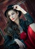 有红色短的礼服和黑帽会议摆在的年轻美丽的深色的妇女肉欲在葡萄酒风景 浪漫神奇夫人 免版税图库摄影