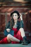 有红色短的礼服和黑帽会议摆在的年轻美丽的深色的妇女肉欲在葡萄酒风景 浪漫神奇夫人 库存照片