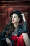 有红色短的礼服和黑帽会议摆在的年轻美丽的深色的妇女肉欲在葡萄酒风景 浪漫神奇夫人 库存图片