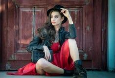 有红色短的礼服和黑帽会议摆在的年轻美丽的深色的妇女肉欲在葡萄酒风景 浪漫神奇夫人 免版税库存图片