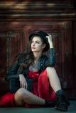 有红色短的礼服和黑帽会议摆在的年轻美丽的深色的妇女肉欲在葡萄酒风景 浪漫神奇夫人 免版税库存照片