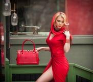 有红色礼服、顶头围巾和袋子的迷人的年轻金发碧眼的女人 红色成套装备的肉欲的华美的少妇有玛丽莲・梦露神色的 免版税库存照片