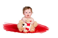 有红色礼服和玩具熊的婴孩 库存照片