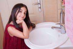有红色礼服的一个美丽的矮小的中东阿拉伯女孩在卫生间里洗她的手 图库摄影