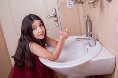有红色礼服的一个美丽的矮小的中东阿拉伯女孩在卫生间里洗她的手 免版税库存图片