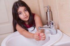 有红色礼服的一个美丽的矮小的中东阿拉伯女孩在卫生间里洗她的手 免版税图库摄影