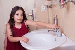 有红色礼服的一个美丽的矮小的中东阿拉伯女孩在卫生间里洗她的手 免版税库存照片