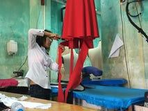 有红色礼服的亚裔裁缝 免版税图库摄影