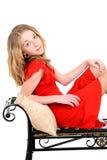有红色礼服的孩子在长凳 免版税库存照片