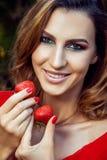 有红色礼服的年轻美丽的愉快的滑稽的拿着草莓夏令时的女孩和构成在公园 库存图片