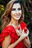 有红色礼服的年轻美丽的愉快的滑稽的拿着草莓夏令时的女孩和构成在公园 图库摄影