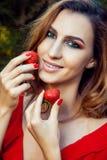 有红色礼服的年轻美丽的愉快的滑稽的拿着草莓夏令时的女孩和构成在公园 免版税库存图片