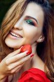 有红色礼服的年轻美丽的愉快的滑稽的拿着草莓夏令时的女孩和构成在公园 免版税库存照片