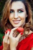 有红色礼服的年轻美丽的愉快的滑稽的拿着草莓夏令时的女孩和构成在公园 免版税图库摄影