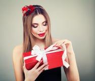 有红色礼物开头礼物盒的俏丽的妇女 图库摄影