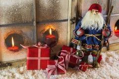 有红色礼物的圣诞老人:圣诞节乡村模式的窗口de 免版税图库摄影
