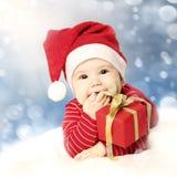 有红色礼物的新年快乐婴孩在雪 免版税库存图片