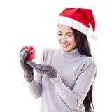 有红色礼物盒和圣诞节帽子的愉快的妇女 免版税库存图片