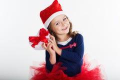 有红色礼物盒的微笑的圣诞老人女孩 免版税图库摄影
