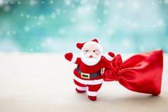 有红色礼物袋子的圣诞老人在被弄脏的大海背景 库存图片