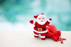 有红色礼物袋子的圣诞老人在被弄脏的蓝色背景 免版税库存照片