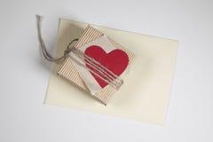 有红色纸心脏的一个箱子,被包裹说谎在信封的绳索 免版税图库摄影