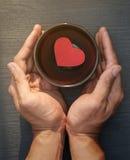有红色纸心脏的两只手在木盘区的一个黑碗 图库摄影