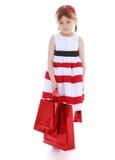 有红色纸袋的可爱的小女孩 免版税库存照片