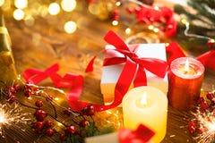 有红色缎带和弓的圣诞礼物箱子,与被包裹的礼物盒,中看不中用的物品,蜡烛的美好的Xmas和新年背景 免版税库存图片