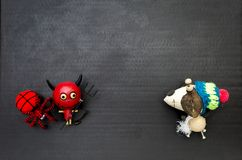 有红色羊毛蜘蛛的愉快的红魔和木滑稽的冬天尾随在黑背景的玩偶 库存图片
