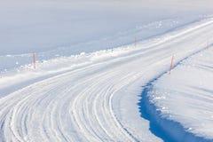 有红色耕的标记的乡下公路在雪 免版税库存照片