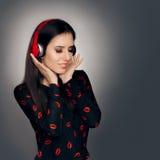 有红色耳机的女孩听爱情歌曲的 库存照片
