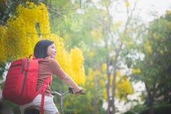 有红色背包骑马自行车的美丽的亚裔女孩在公园 免版税库存照片