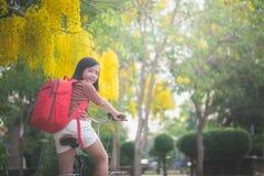 有红色背包骑马自行车的美丽的亚裔女孩在公园 图库摄影