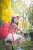 有红色背包骑马自行车的美丽的亚裔女孩在公园 库存图片