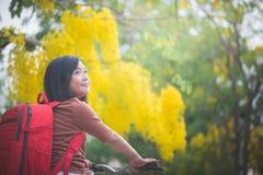 有红色背包骑马自行车的美丽的亚裔女孩在公园 免版税图库摄影