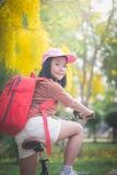 有红色背包骑马自行车的美丽的亚裔女孩在公园 库存照片