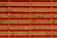 有红色背景水平的板的木篱芭 库存图片